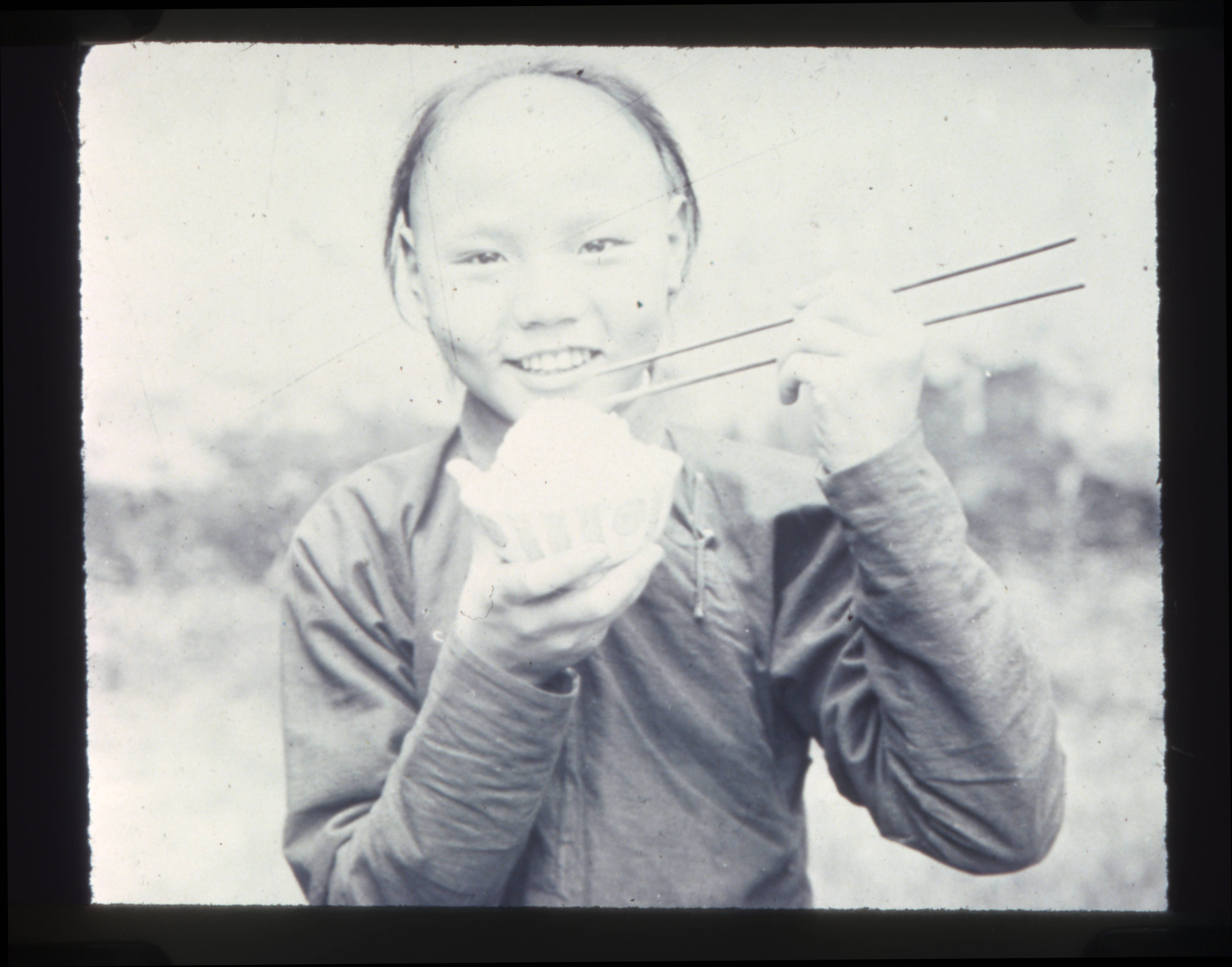 File young chinese person eating rice with chopsticks for 1900 asian cuisine