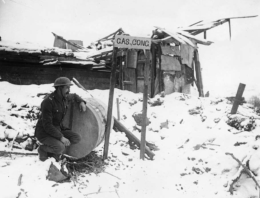 A sentry watching for any sign of gas attacks. He is squatting beside a notice which reads, 'gas gong'. The gong appears to be a large metal drum, like an oil drum. The drumstick is hanging from a string tied to the notice.The fear of gas is described in Wilfred Owen's poem, 'Dulce et Decorum est', ' GAS! Gas! Quick, boys! ..  An ecstasy of fumbling, Fitting the clumsy helmets just in time; But someone still was yelling out and stumbling / And floundering like a man in fire or lime ..  Dim, through the misty panes and thick green light / As under a green sea, I saw him drowning.' [Original reads: 'The Gas Sentry.'] http://digital.nls.uk/74549298