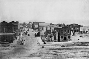 About a dozen one- and two-story buildings, several of which are damaged, line a dirt road that intersects with three railroad tracks in the foreground