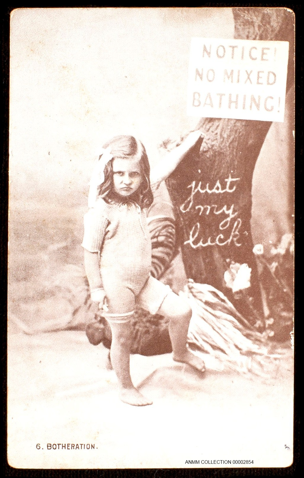 Photographic postcard of a young girl dressed for the beach of her time, standing under a sign inscribed, `Notice No Mixed Bathing