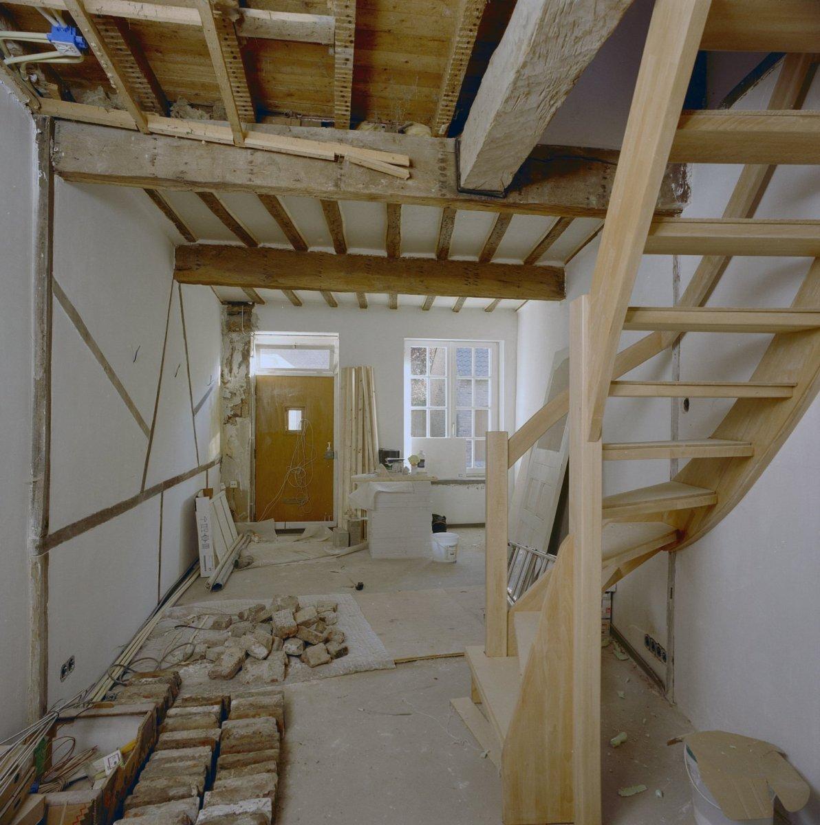 File interieur woonkamer met vakwerkwand voordeur en open houten trap tijdens verbouwing - Deco houten trap ...