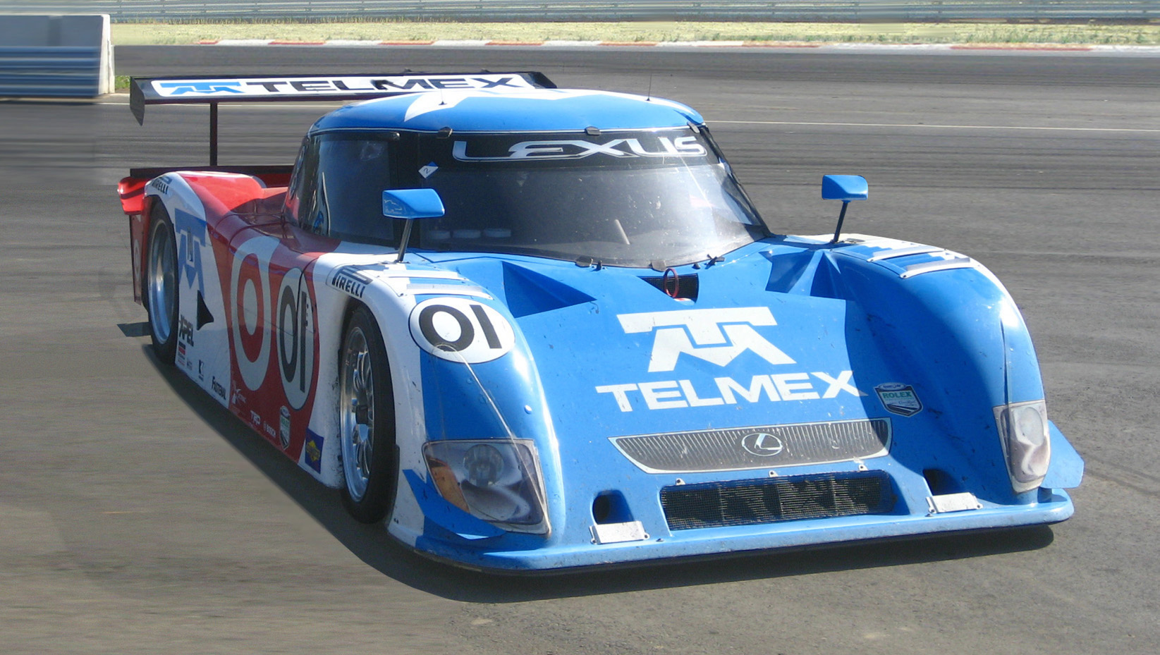 alt=Forward angle view of a racecar on a track; the car is labeled '01', 'Lexus', and 'Telmex'.
