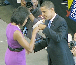 "The Obamas face each other and bump fists on stage. She wears a purple dress and he wears a dark suit. Several signs read ""CHANGE WE CAN BELIEVE IN"" and several photographers take photos."