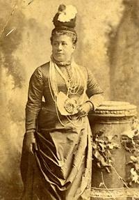 Photograph of Queen Kapiʻolani standing looking to her left. She is wearing a hat and a necklace of several strands of Ni'ihau shells.
