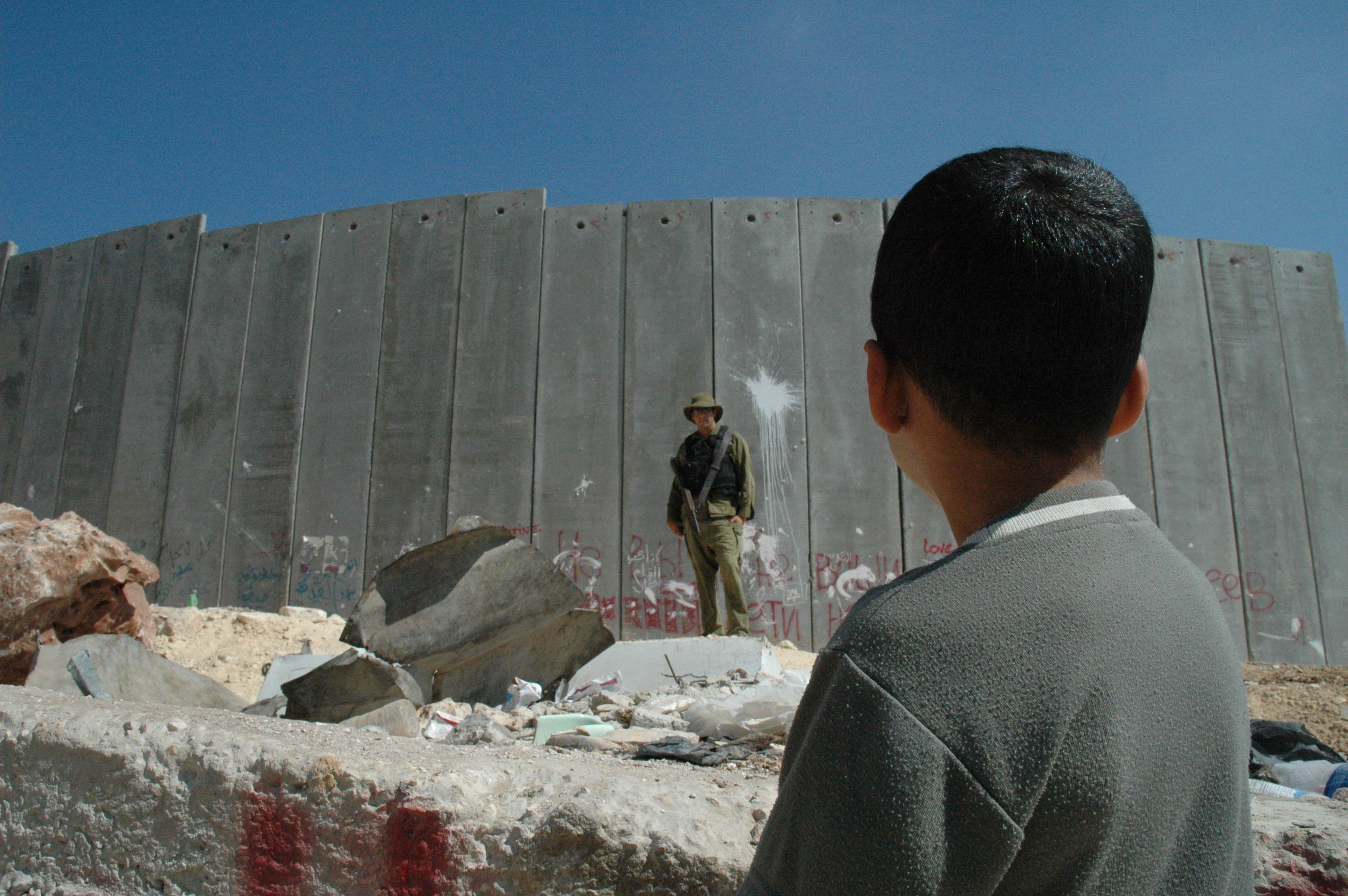 A boy and soldier in front of the West Bank Barrier