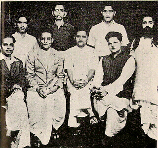 A group photo of people accused in the Mahatma Gandhi's murder case. Standing: Shankar Kistaiya, Gopal Godse, Madanlal Pahwa, Digambar Badge. Sitting: Narayan Apte, Vinayak D. Savarkar, Nathuram Godse, Vishnu Karkare