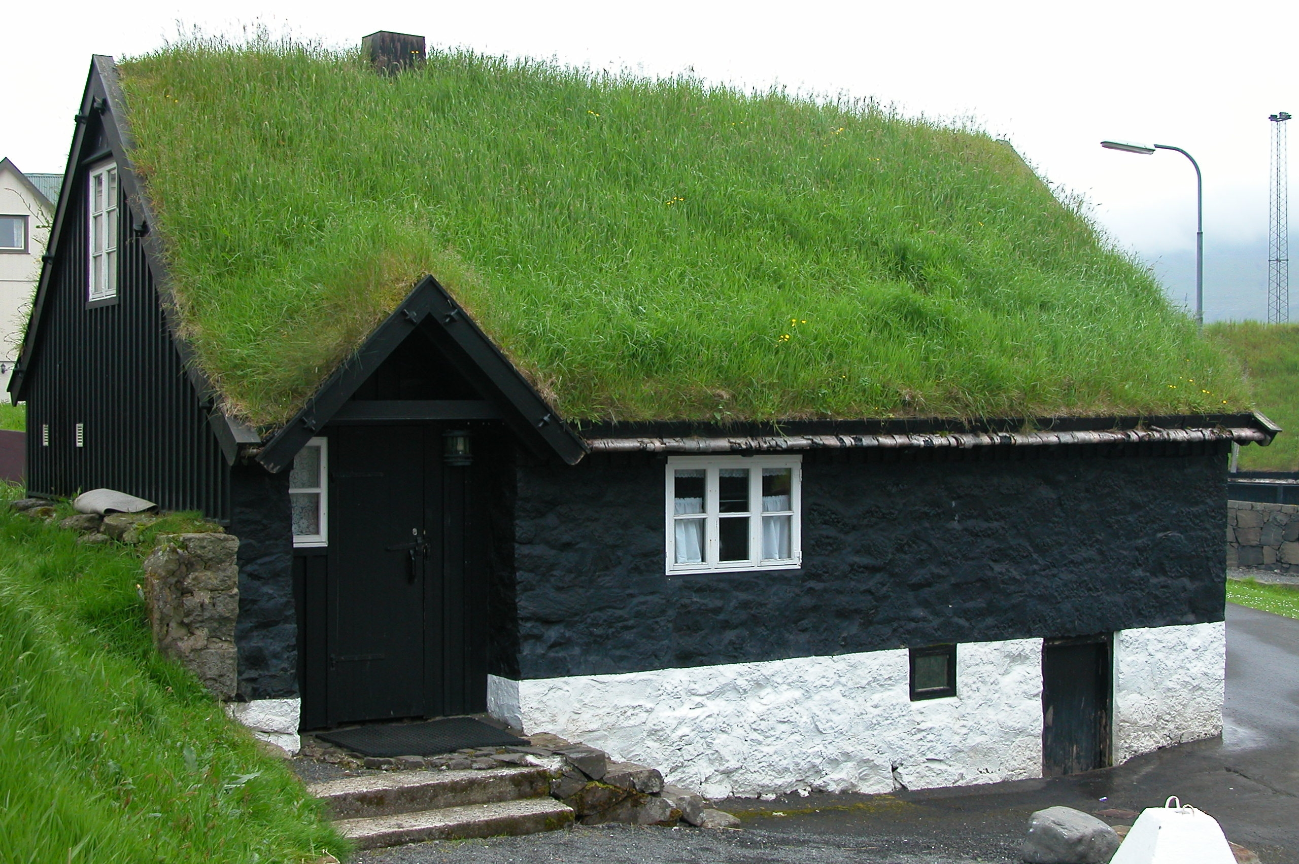 A black-and-white painted house has a grassy roof