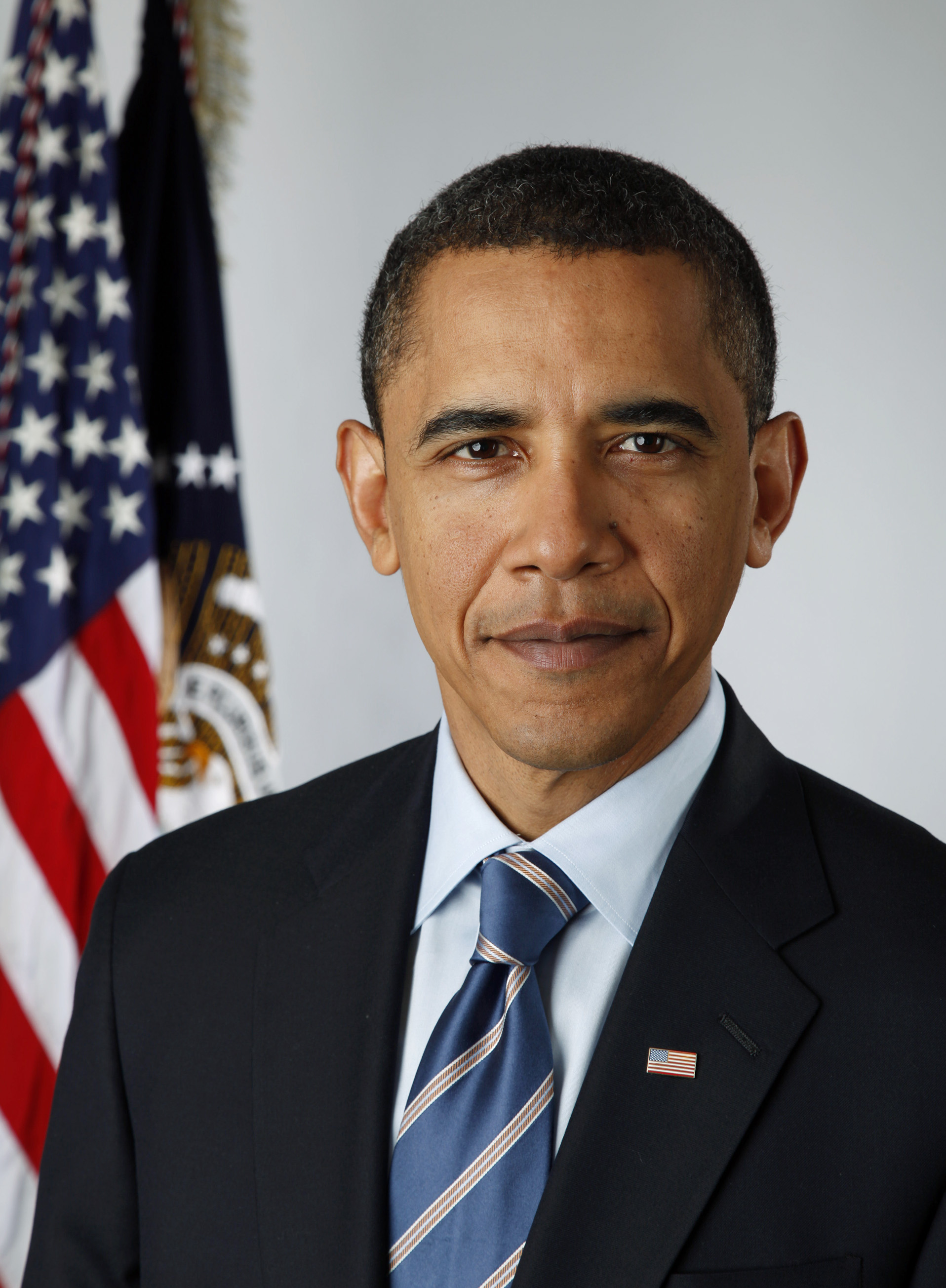 A portrait shot of Barack Obama, looking straight ahead. He has short black hair, and is wearing a dark navy blazer with a blue striped tie over a light blue collared shirt. In the background are two flags hanging from separate flagpoles: the American flag, and the flag of the Executive Office of the President.