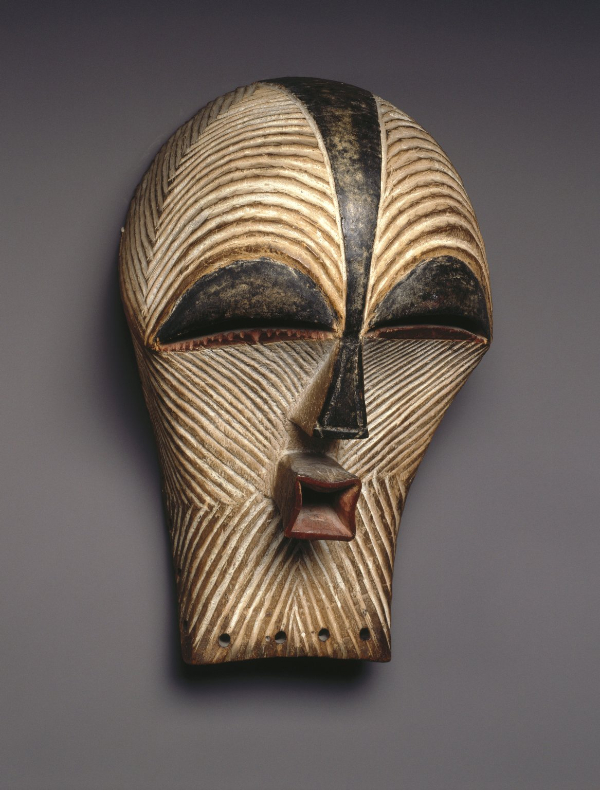 a description of the songye masquerade Description: the elaborate hairstyle of this mask is representative of a mature baule woman it would have been danced at masquerades with the masquerader concealed by raffia the performance of the masquerade is to remind everyone of the social order.