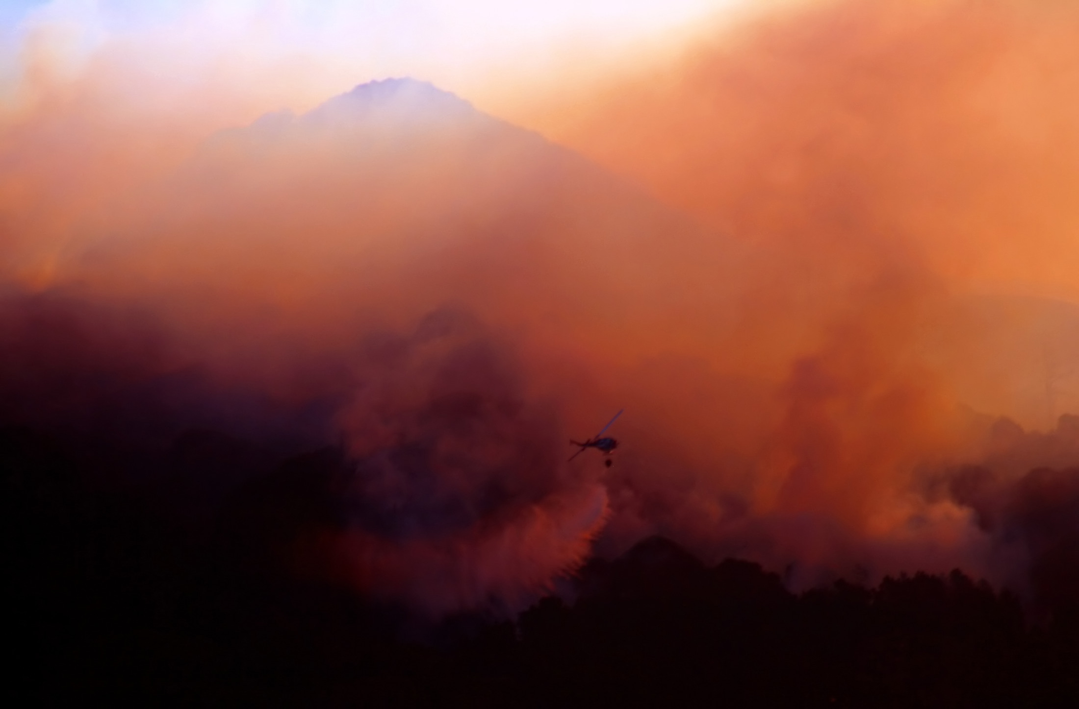 A fire helicopter is used to fight a wildfire
