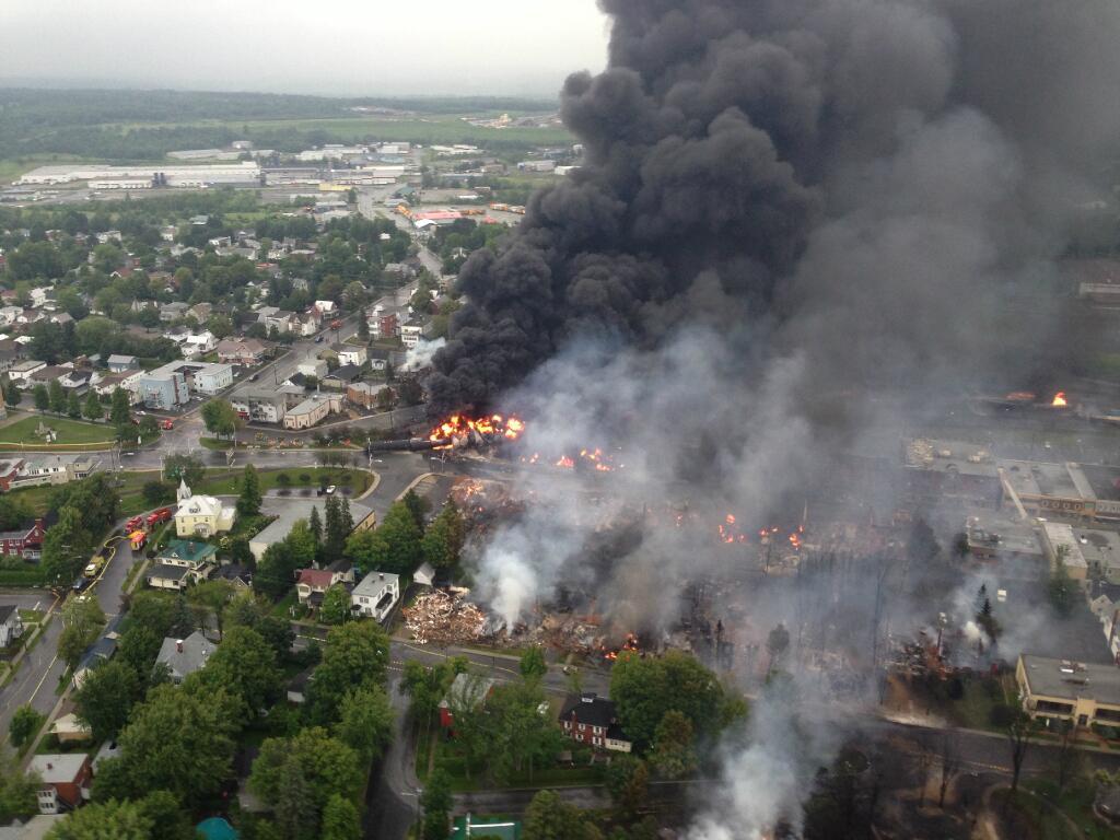Photo: vue de l'hélicoptère au-dessus de la tradégie du Lac Mégantic. Un secteur de la ville est en feu, les maisons rasées, énormes colonnes noires et blanches de fumée.