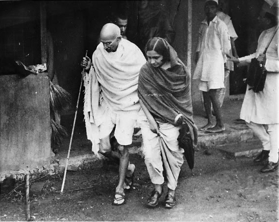 File:Mahatma Gandhi with a bamboo staff strolling through a village with assistance by a woman congress-worker - 1942.jpg