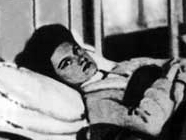 A Caucasoid woman with dark hair is lying in a hospital bed; she is looking at the camera, pictured from her mid-torso through the wall behind her head.