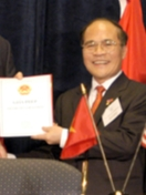 a smiling nearly bald man, wearing glasses, a suit and a red tie while holding up a piece of paper