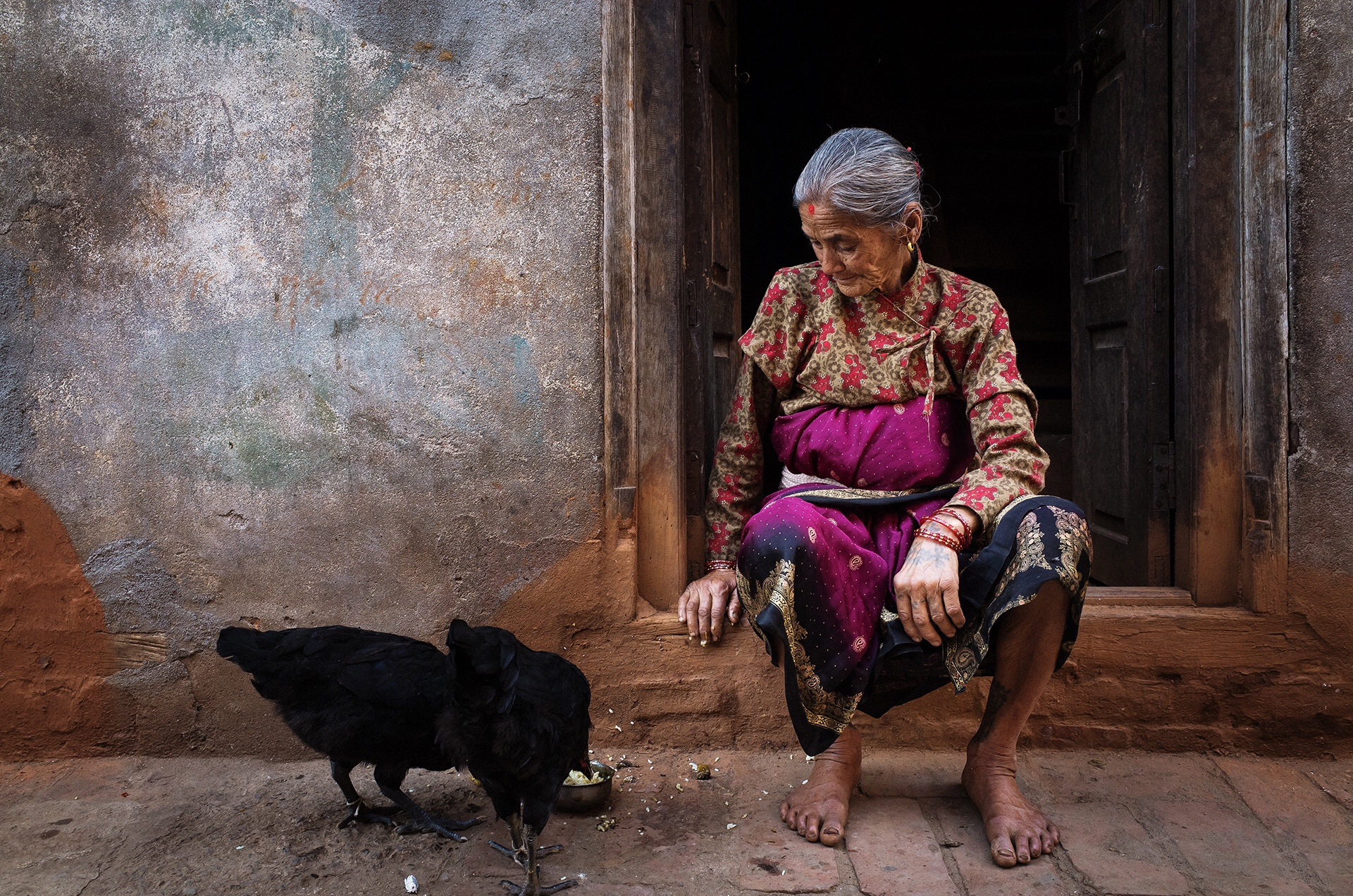 A gray-haired woman in colorful native dress, sitting in a doorway, watching two black hens scratching for food