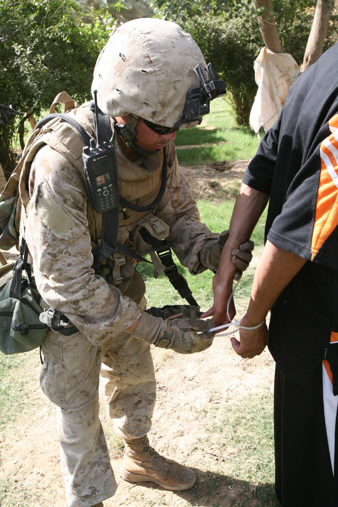 солдат использует пластиковые наручники