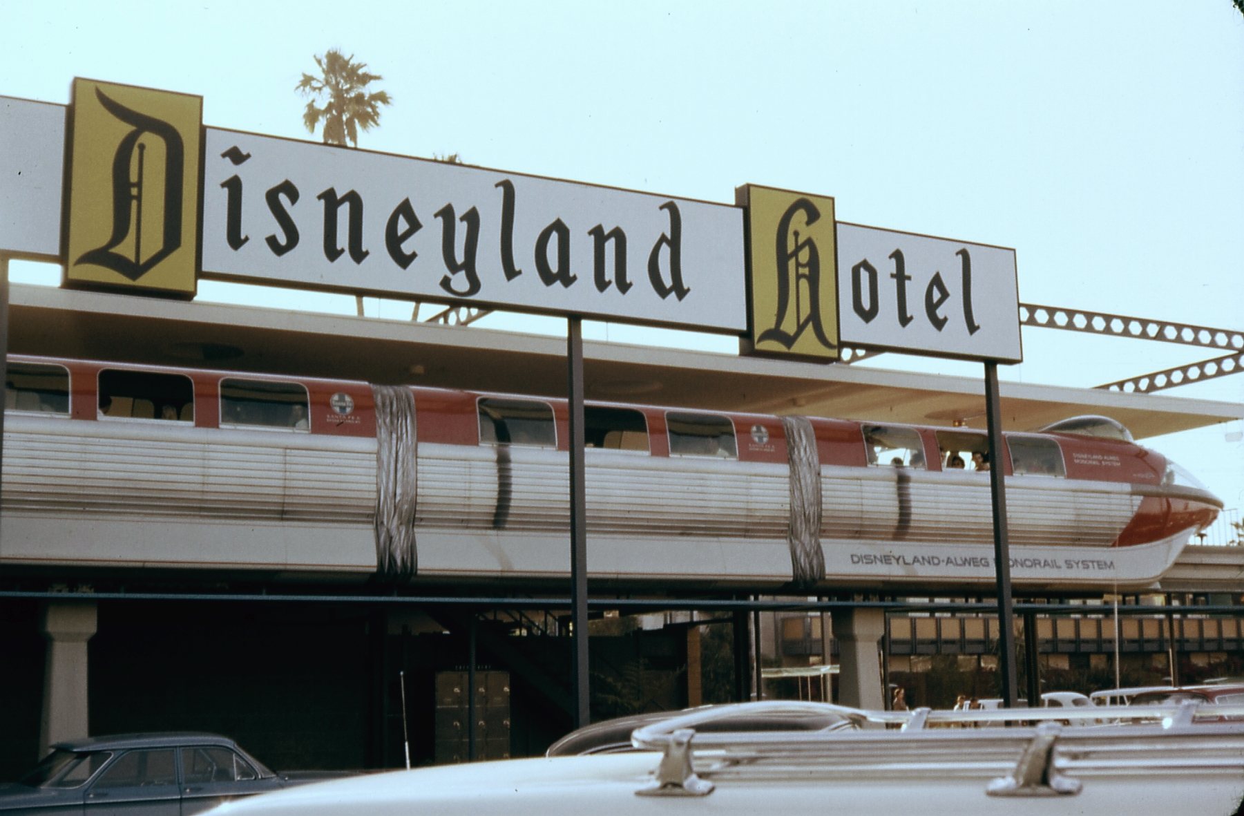 The original red Mark I ALWEG Monorail train, with one car added, and then designated Mark II. Both trains were created especially for Disneyland. The other train was identical, but blue color. Seen at the Disneyland Hotel station, in August, 1963