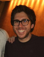 Amir Blumenfeld smiling at the camera, with a hand on his shoulder