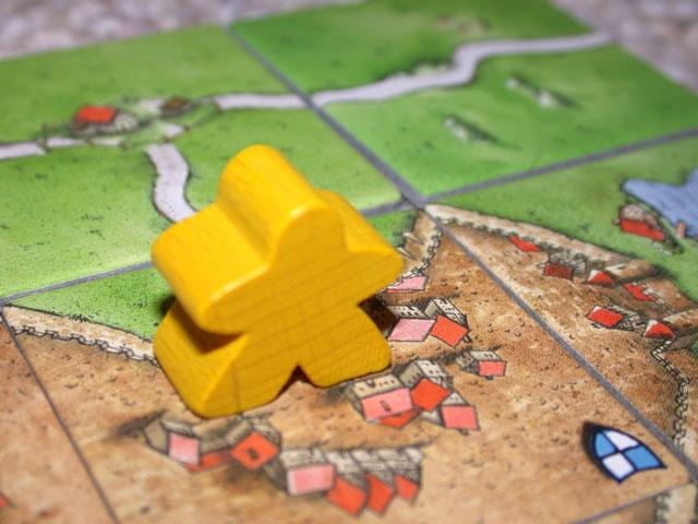 Meeple jaune sur une tuile de Carcassonne