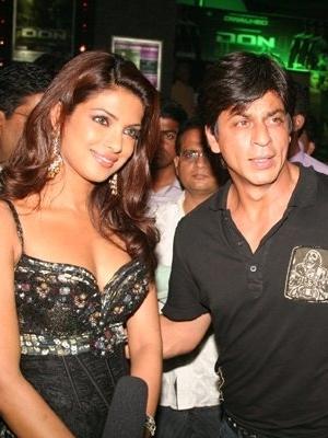 Shah Rukh Khan standing beside Priyanka Chopra at film premiere