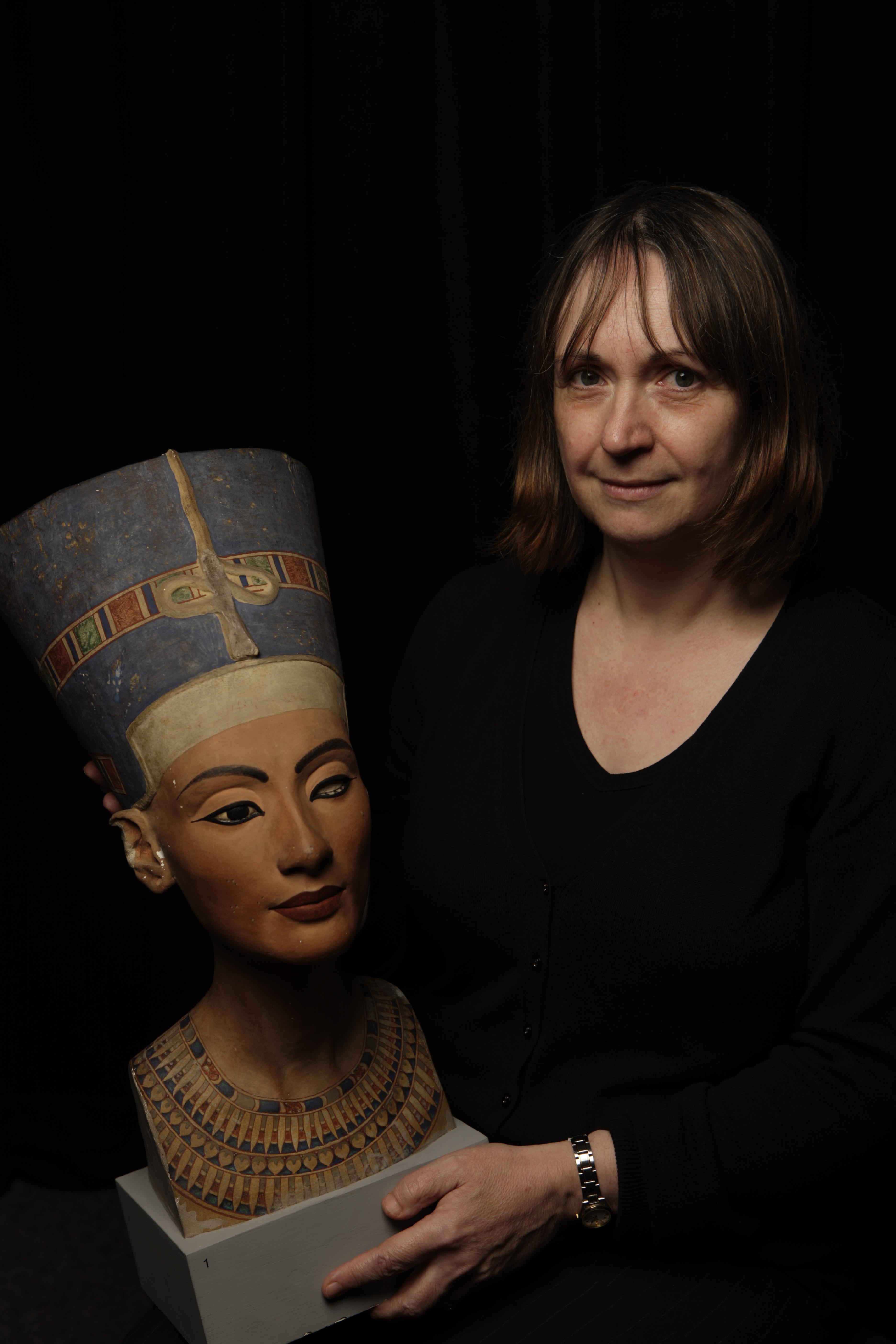 Joyce Tyldesley holding a replica Nefertiti bust.