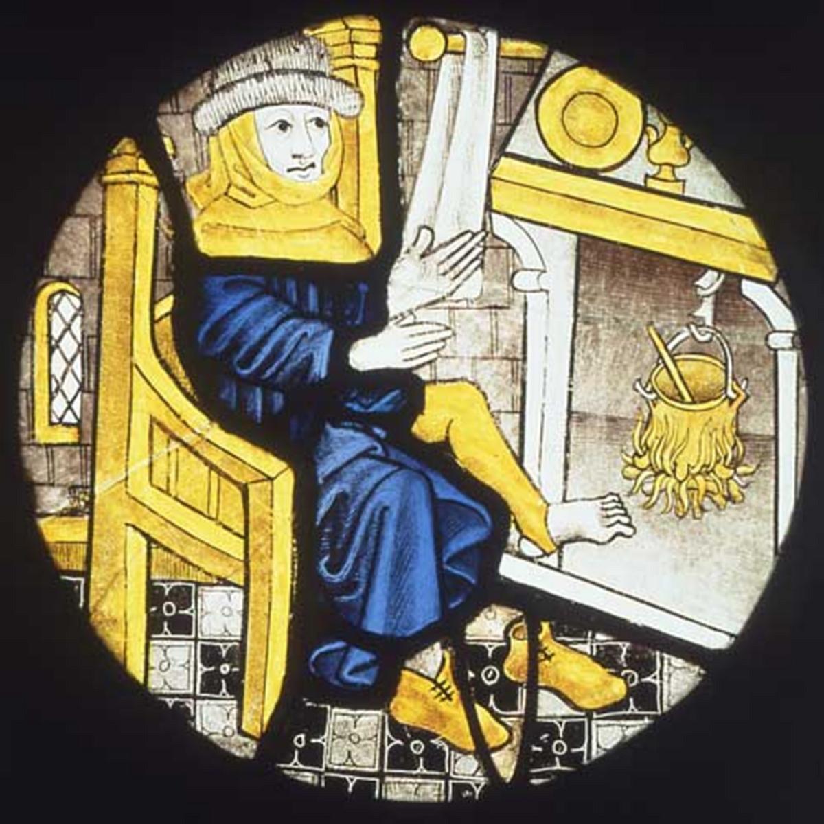 Der Januar am Feuer. Glasmalerei aus Norwich/UK, um 1500.