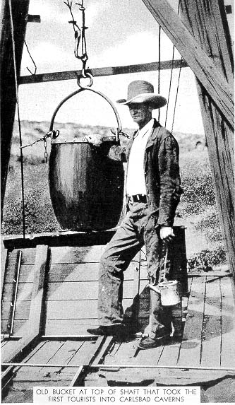 Jim White standing next to a guano bucket atop the guano shaft at Carlsbad Caverns. The bucket was used to carry the first tourists into the caverns. He is holding one of his homemade kerosene lanterns. Jim White Guano Bucket.jpg