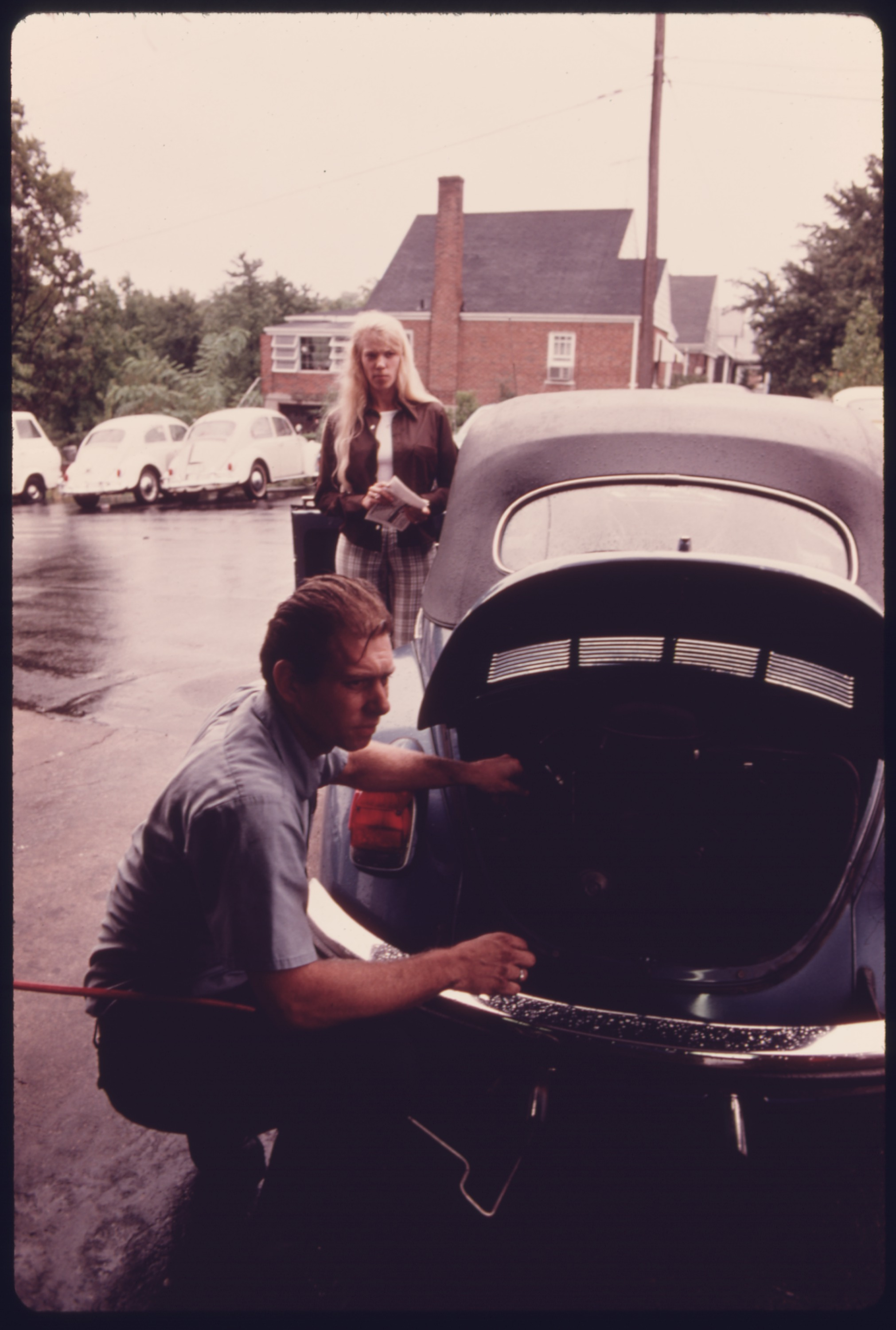 File:SERVICE STATION MECHANIC ADJUSTS THE ENGINE FOR A YOUNG WOMAN ...