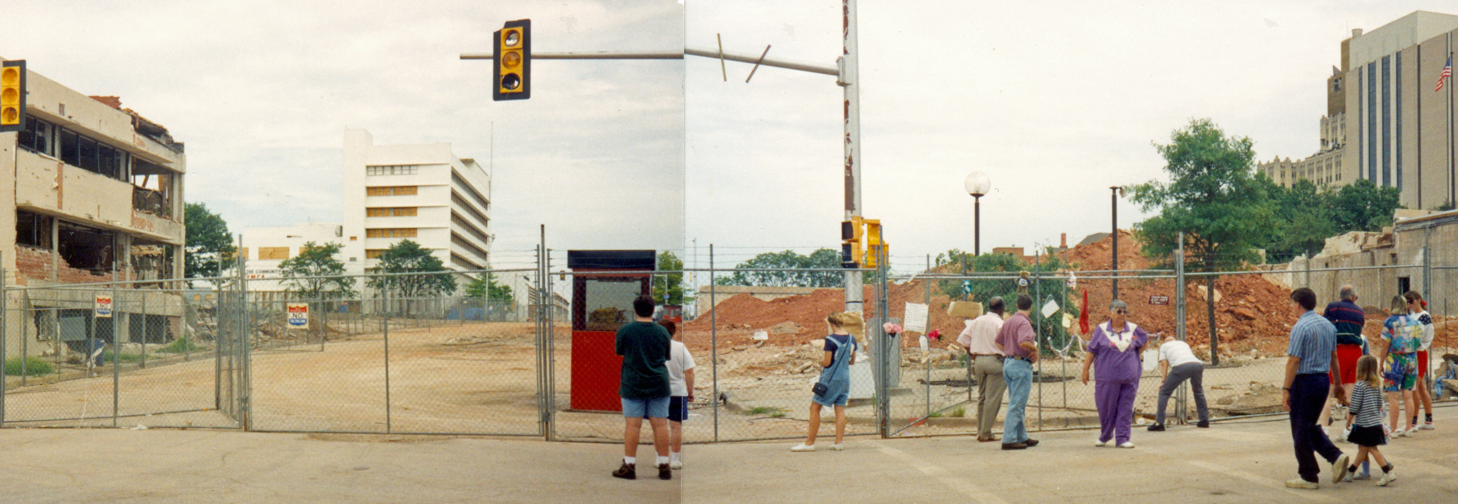 Two images are stitched together showing the site of where the building stood prior to its demolition. A crowd of people are visible in front of the chain link fence blocking entrance to the site. Large piles of dirt can be seen on the site as well as damage to nearby buildings.