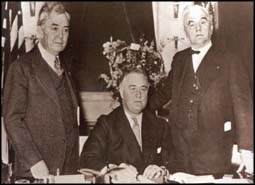 Roosevelt signing the Rural Electrification Act in 1935, with Rankin (left) and Senator George W. Norris (R-Nebraska) (right).