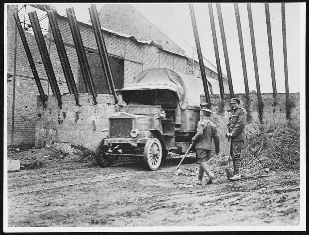 Canadian officers beside German fortifications at Pronville, France, during World War I. Canadian officers demonstrate how their lorry was just wide enough to breach the gap in the German fortifications at Pronville. German fortifications were often superior in design and construction to Allied ones. The Germans originated the use of concrete in building dug-outs and trench systems, and the scale of the concrete, iron and wire construction in the picture demonstrates the German desire to build strong, lasting defences.Pronville is a town in the Pas de Calais region in north-east France. It was in this area that Canadian troops were most heavily concentrated in the final months of the war. [Original reads: 'In PRONVILLE the Germans erected the elaborate ferro-concrete trap seen in the picture. The gap is large enough for a lorry but would have stopped a tank. To the consternation of the enemy the Canadians advanced here without the support of the dreaded land ships.'] http://digital.nls.uk/74549230