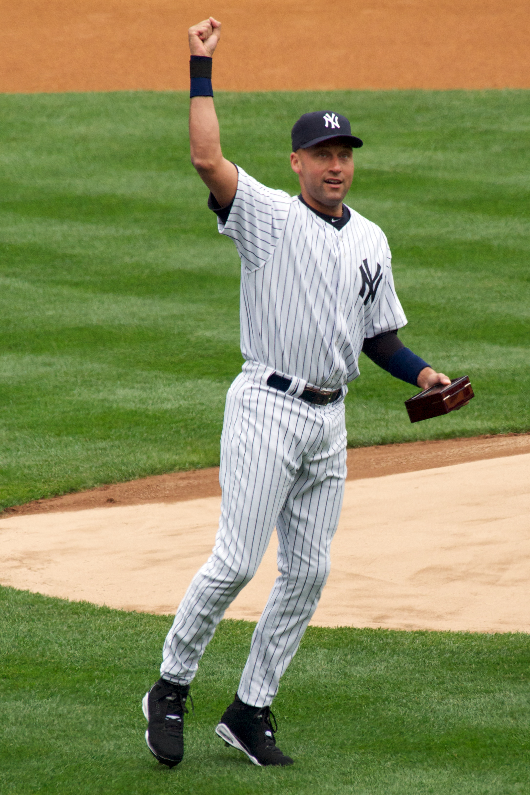 A man in a white baseball uniform with navy pinstripes raises his right arm in the air while holding a box in his left hand.