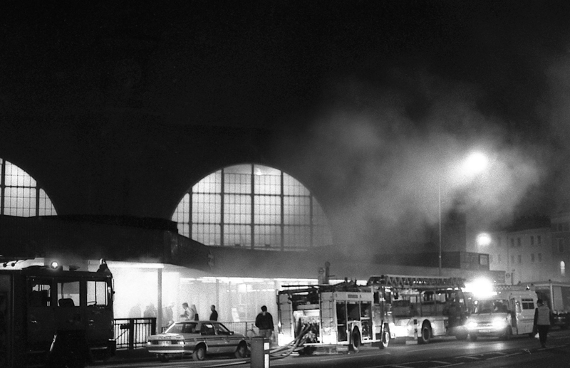 A black and white photograph of King's Cross underground station during the fire with billowing smoke, station lights and fire engines.
