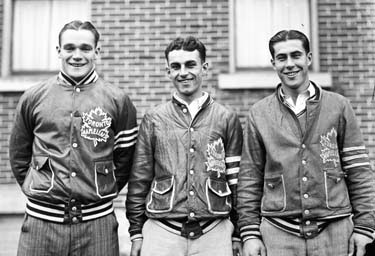 three young men stand side by side.  Each has short, dark hair parted in the middle and are wearing identical team jackets with a stylized maple leaf logo on the left breast.