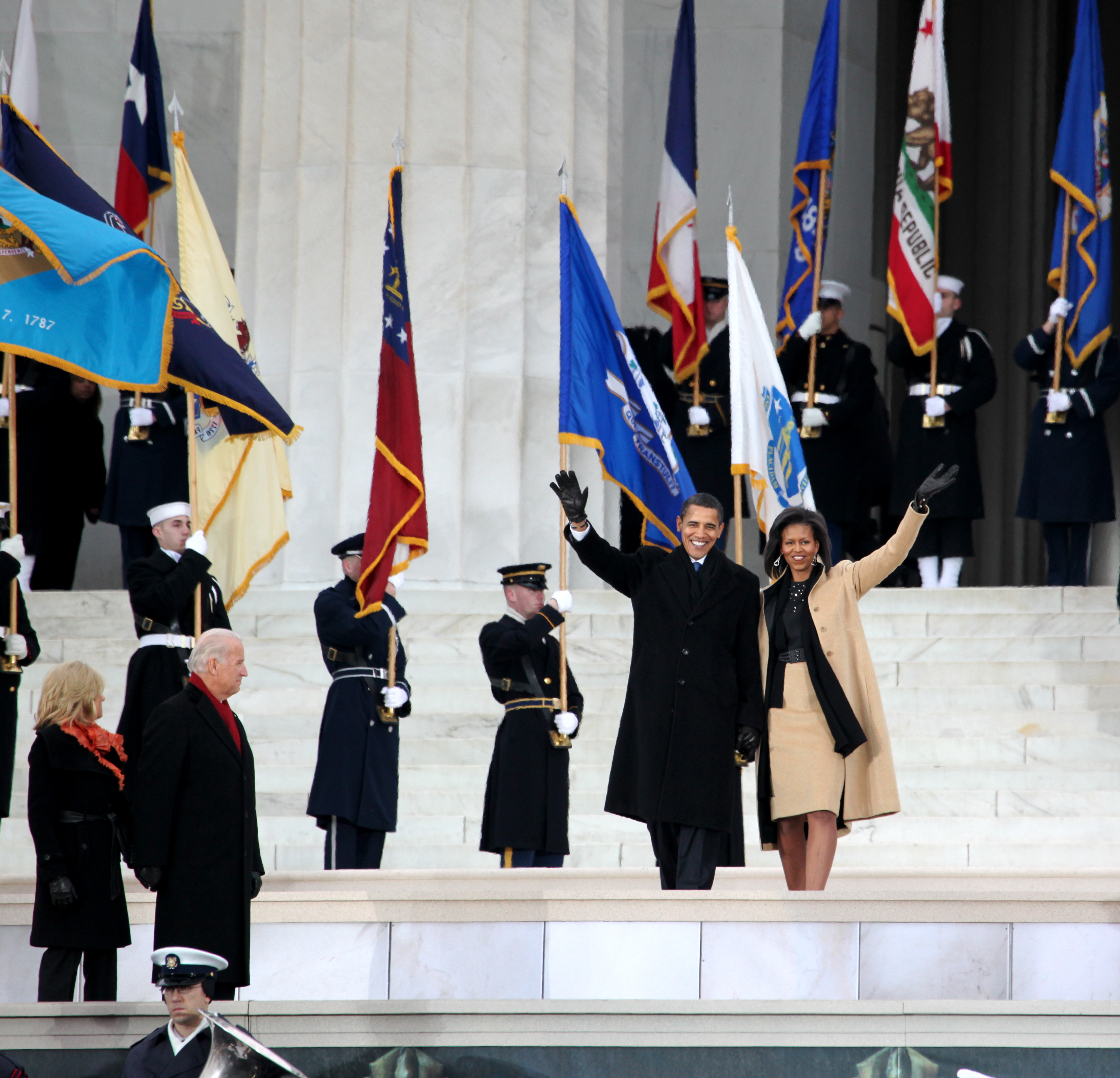 The Obamas wave as they walk past military flagbearers in the background while a couple stands in the foreground.