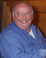 A man in his fifties, balding and portly, is shown smiling to the left of the camera.