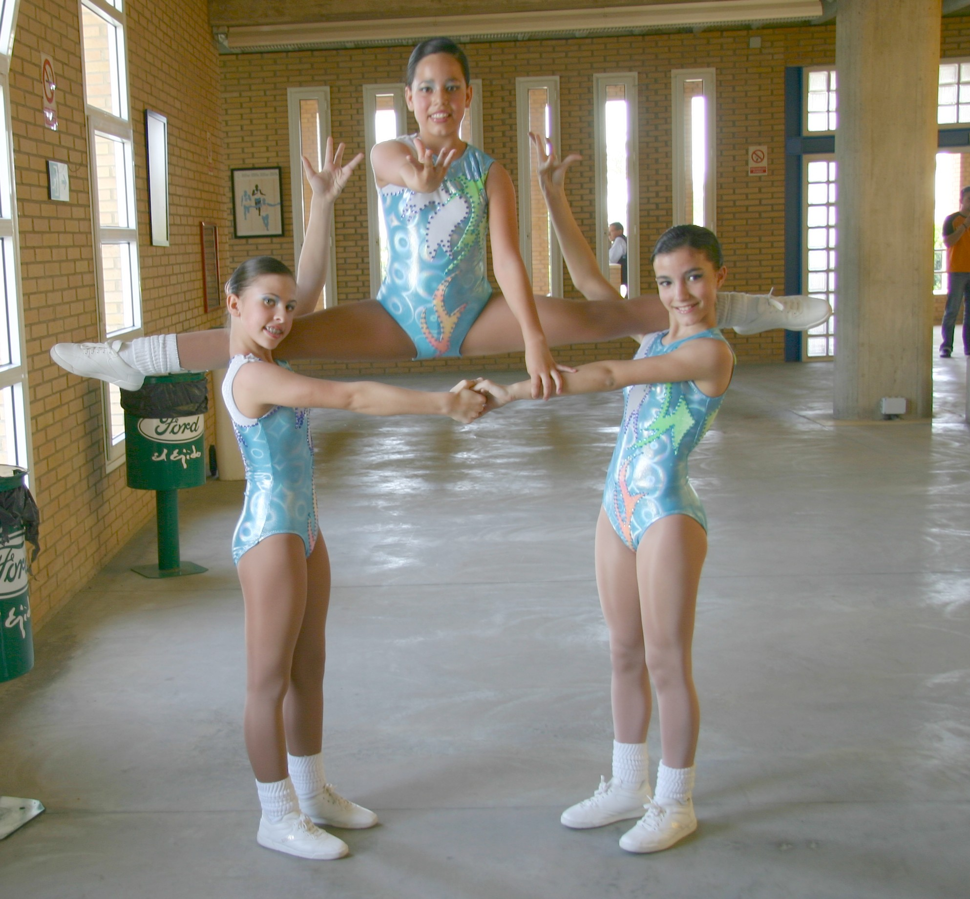 3 young girls in aerobic poses; 1 of them doing splits on their shoulders