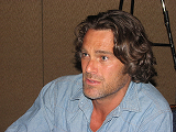An image of a man with long hair and a button-down shirt; he is looking away from the camera.