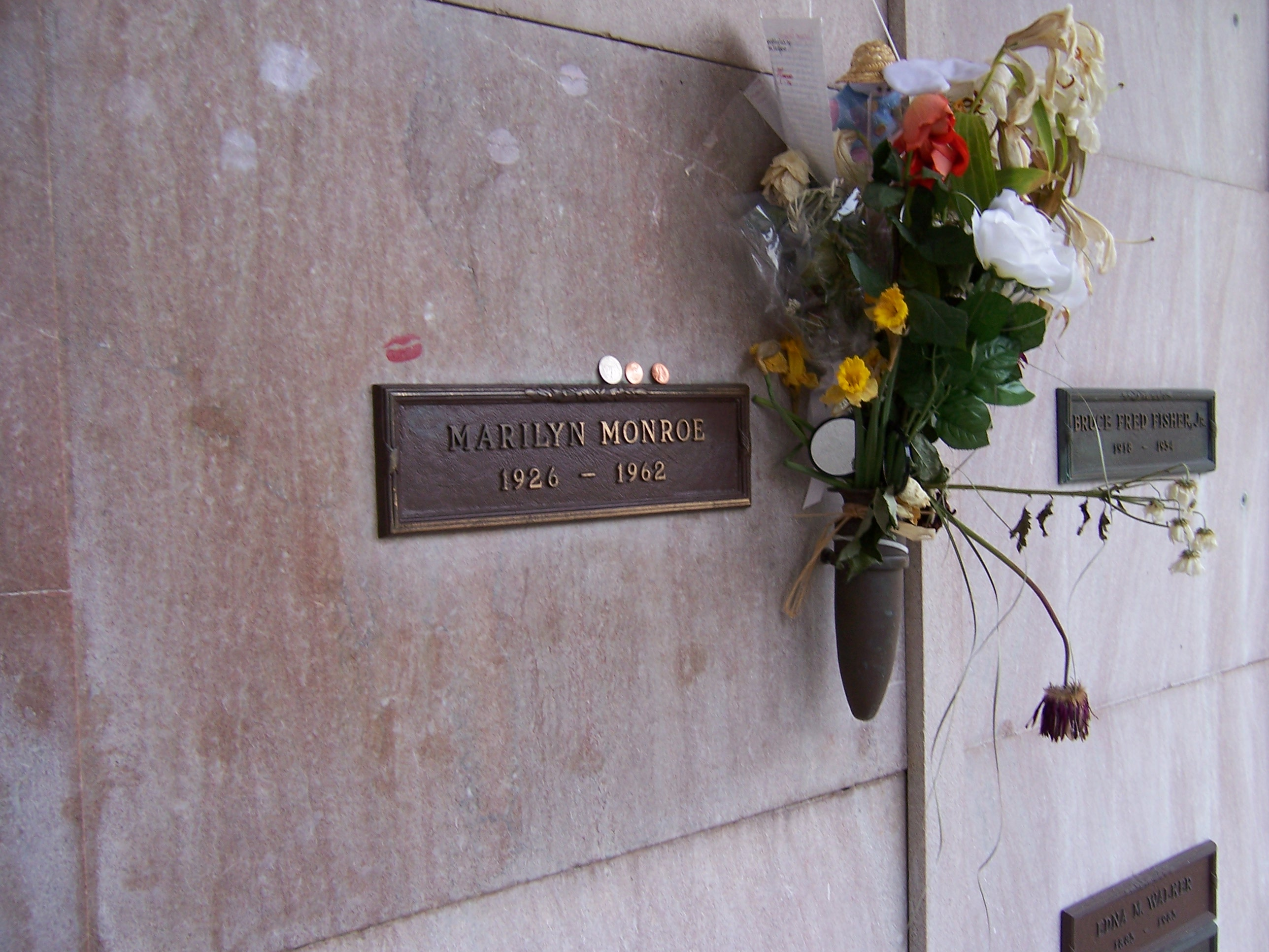 "Photo of Monroe's crypt, taken in 2005. ""Marilyn Monroe, 1926–1962"" is written on a plaque. The crypt has some lipstick prints left by visitors and flowers are placed in a vase attached to it."