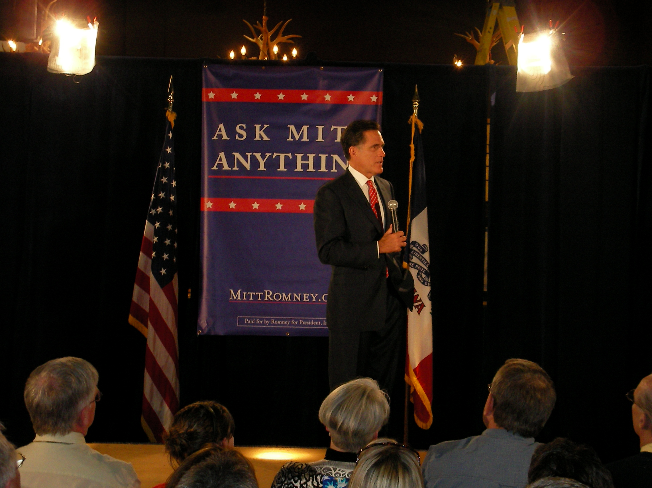 Mitt Romney addressing an audience from atop a stage