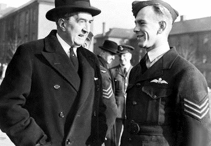 Two men talking, one in dark overcoat with broad-brimmed hat, the other in dark military uniform with forage cap