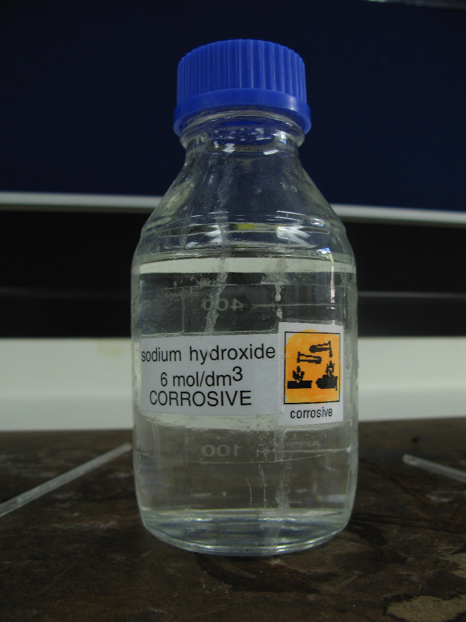 By Matthew Sergei Perrin from Auckland, New Zealand (Sodium Hydroxide 6mol Corrosive Lab Chemicals) [CC BY 2.0 (http://creativecommons.org/licenses/by/2.0)], via Wikimedia Commons