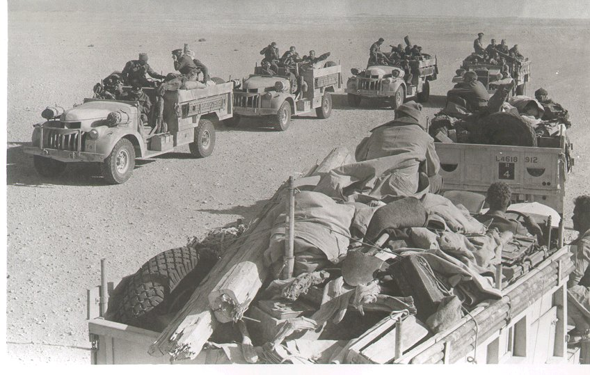 six vehicles, each with a number of men on board; the one closest is overloaded with equipment