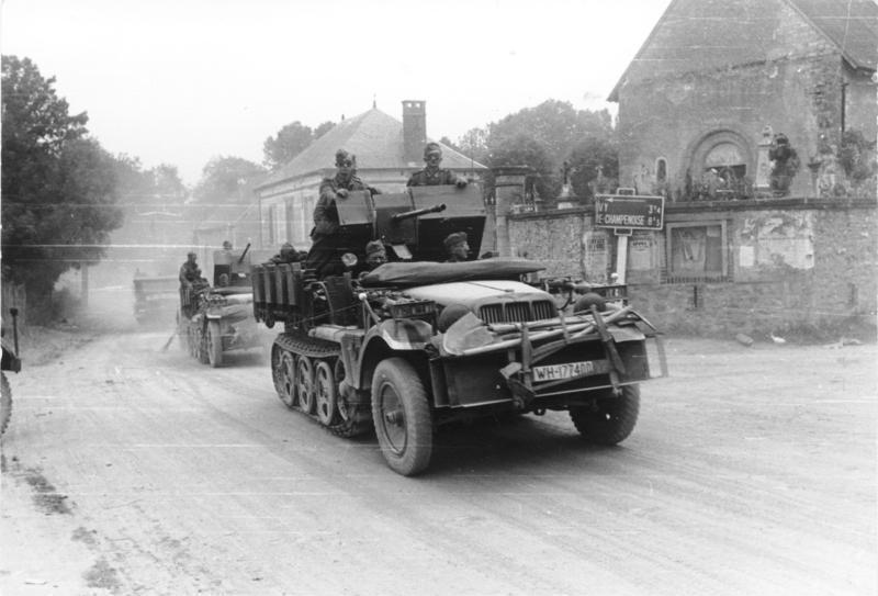 Bundesarchiv_Bild_101I-055-1572-30%2C_Frankreich%2C_Zugmaschine_mit_Flak_in_Ortschaft.jpg