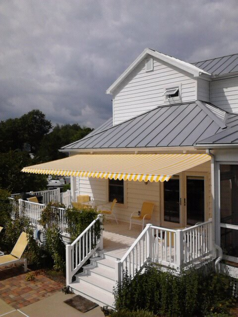 colourful yellow and white striped retractable awning on weatherboard home