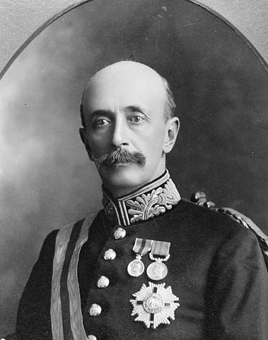 Upper body of a bald man with a large moustache.  He is in a military uniform with several medals pinned to his left chest.