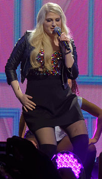 Meghan Trainor performing in a colorful top, black jacket and skirt