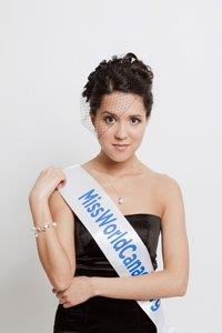 A photograph of a woman with brown hair and brown eyes looking at the viewer and wearing a black dress and a white sash with blue letters