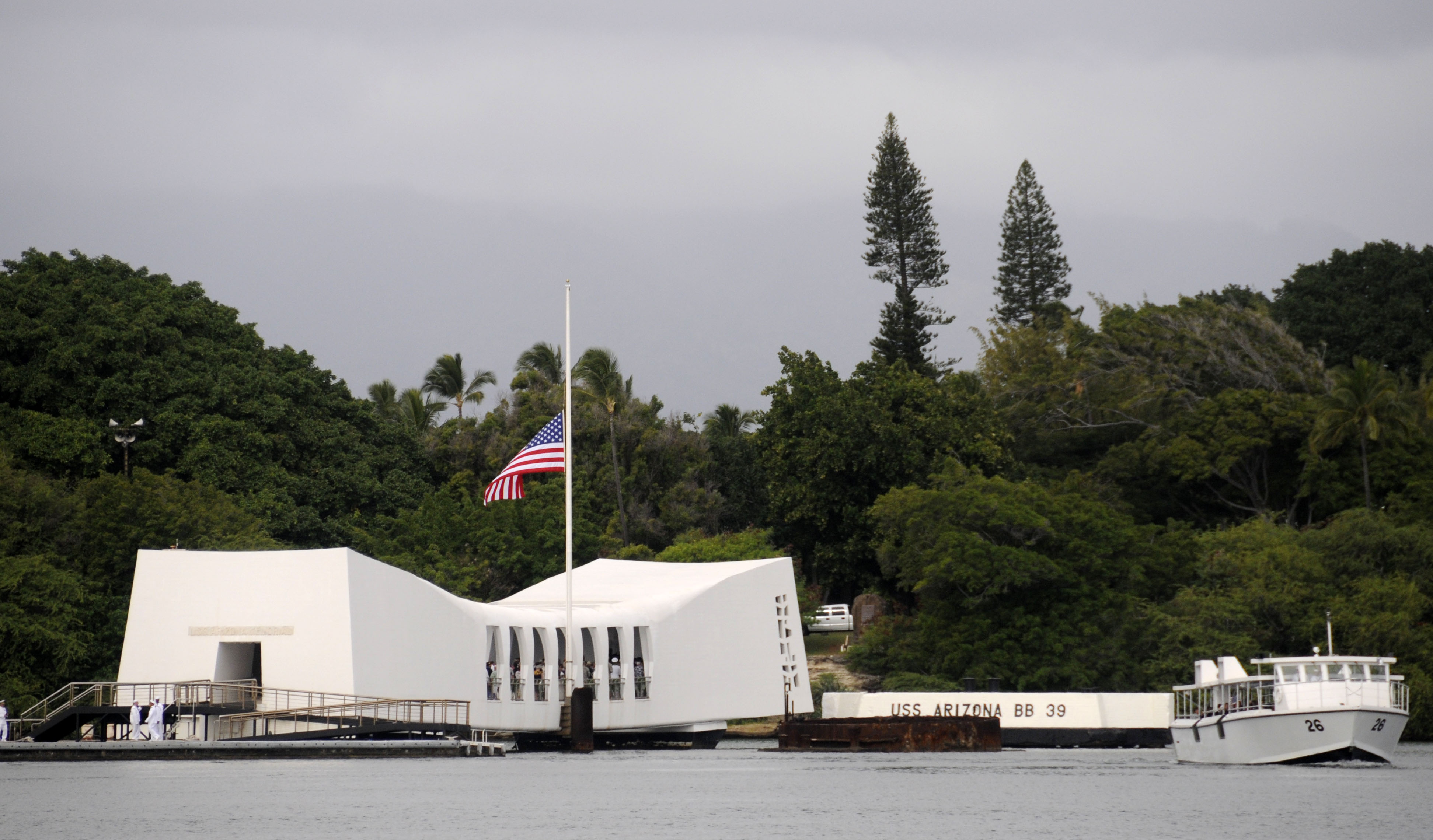 uss arizona in pacific ocean with a flag at half staff, with dark green trees in the background