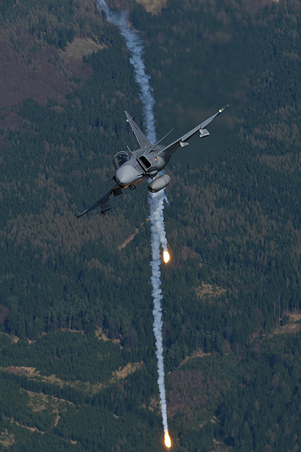 Head on view of fighter jet banking right while releasing flares against a background of green woodland.